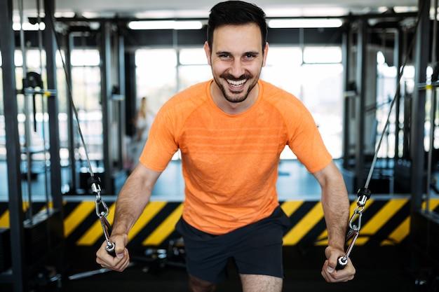 피트 니스 기계에 체육관에서 운동 하는 남자