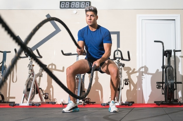 Man working out with rope in functional training fitness gym