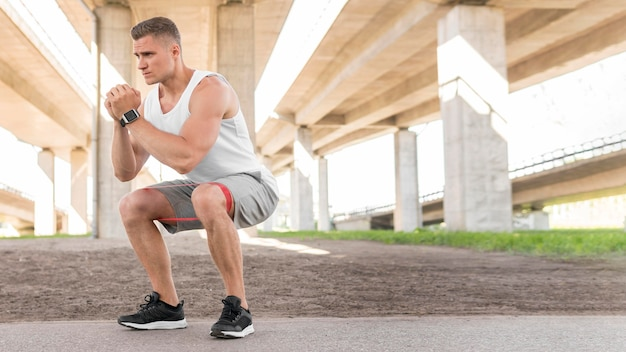 Man working out with a stretching band with copy space
