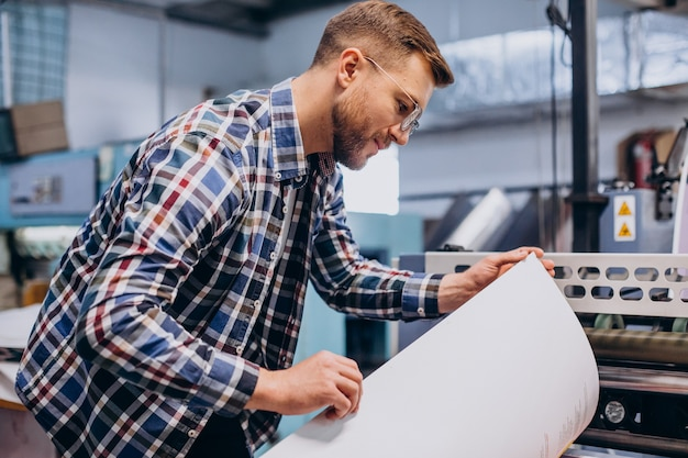 Man working in printing house with paper and paints Premium Photo