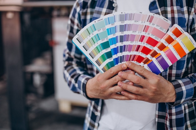 Man working in printing house with paper and paints
