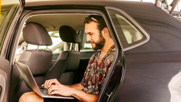 Man working remotely on back seat of car
