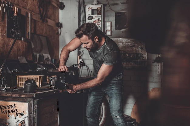 Man working in repair shop. confident young man using work tool while working in repair shop