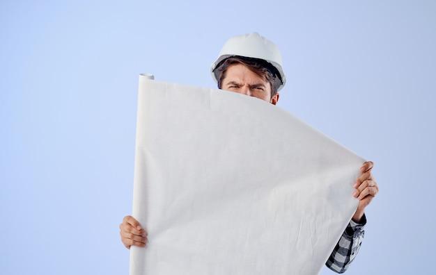 A man in a working uniform an engineer blueprints a project plan professional construction work