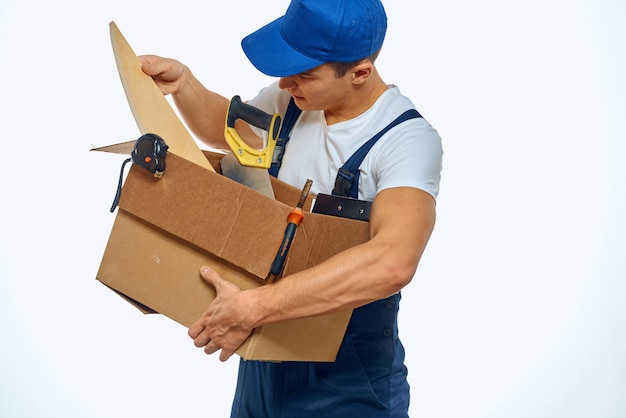 A man in a working uniform with a box in his hand loading a delivery service.