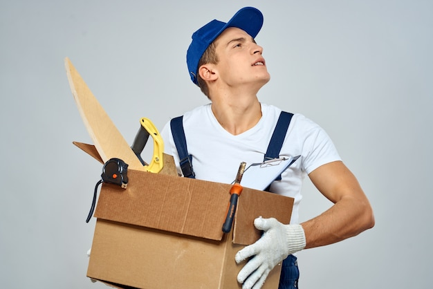 Man in working uniform with a box in his hands tools loader delivery light space.