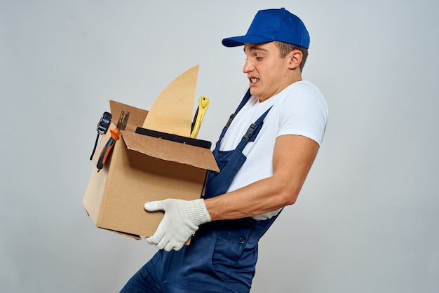 Man in working uniform with a box in his hands