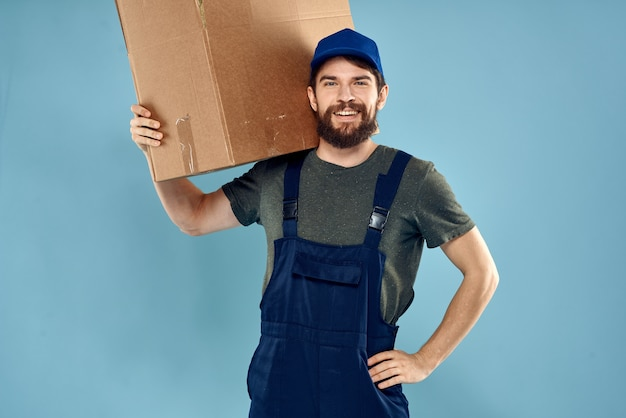 A man in working uniform with boxes in the hands of a carriage delivery service blue space