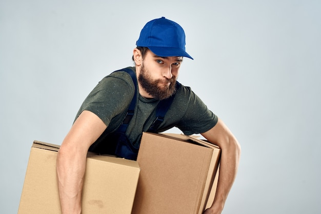 Man in working uniform with boxes in hands delivery loading lifestyle.