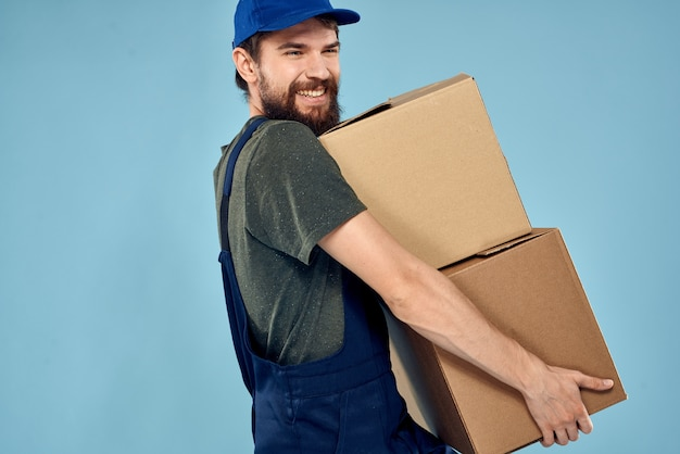 Man in working uniform with boxes in hands delivery service blue space
