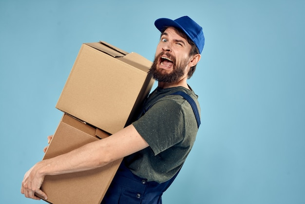 Man in working uniform with boxes in hands delivery service blue