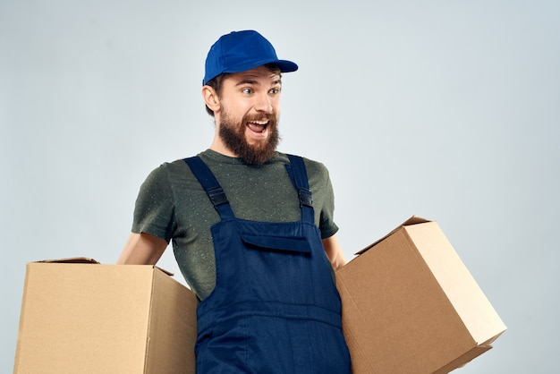 Man in working uniform with boxes in hands