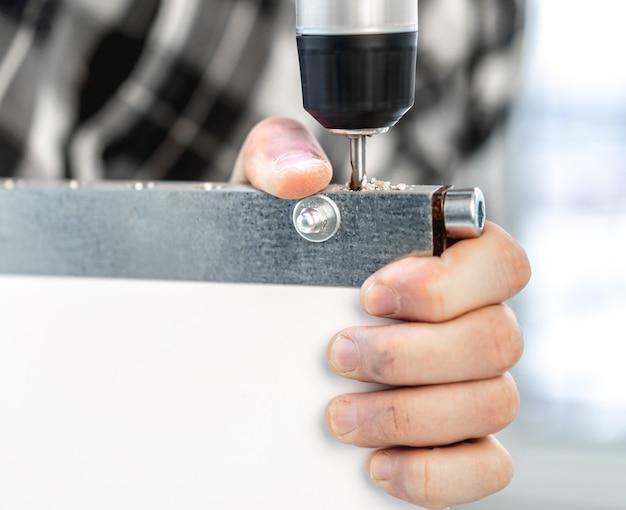 Человек, работающий с помощью электродрели в процессе производства деревянной мебели