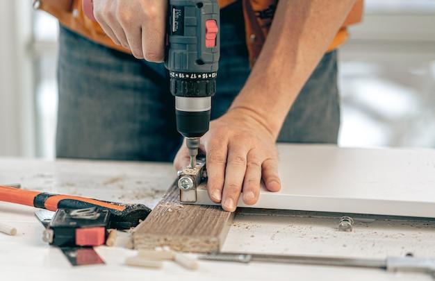 Человек, работающий с помощью электрической отвертки во время производства деревянной мебели в мастерской