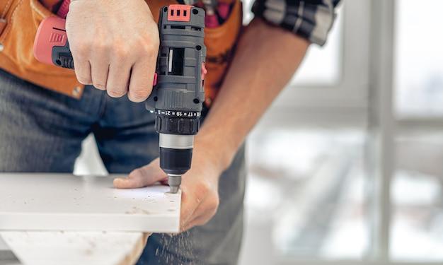 Человек, работающий с помощью электрической отвертки во время производства деревянной мебели