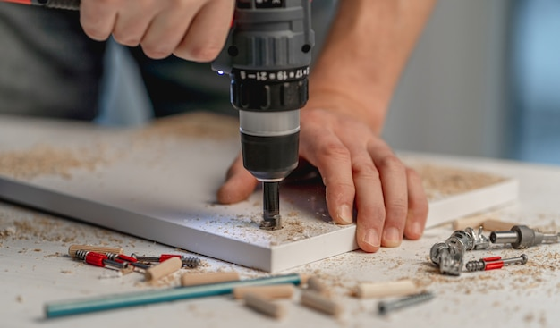 Man working using electric screwdriver during process of wooden furniture manufacturing in workshop