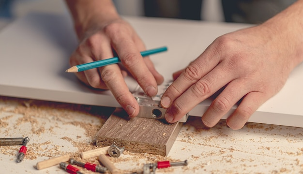 Man working using electric screwdriver during process of wooden furniture manufacturing