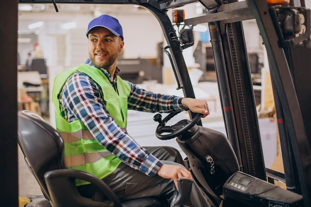 Man working at warehouse and driving forklift