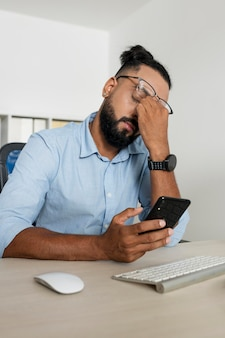 Man working while checking his phone