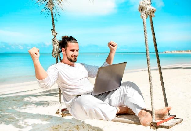 Человек, работающий с ноутбуком на гамаке в выигрыше шоу на пляже