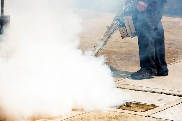 Человек, работающий с дымовой машиной в люк для борьбы с вредителями