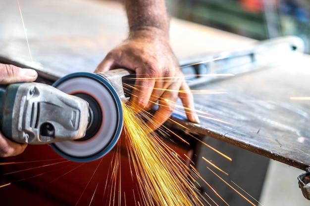 Человек, работающий с угловой шлифовальной машиной с блестками от нее