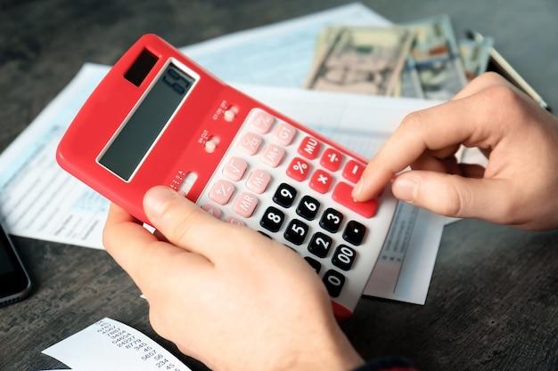 Человек, работающий с калькулятором и документами. налоговая концепция