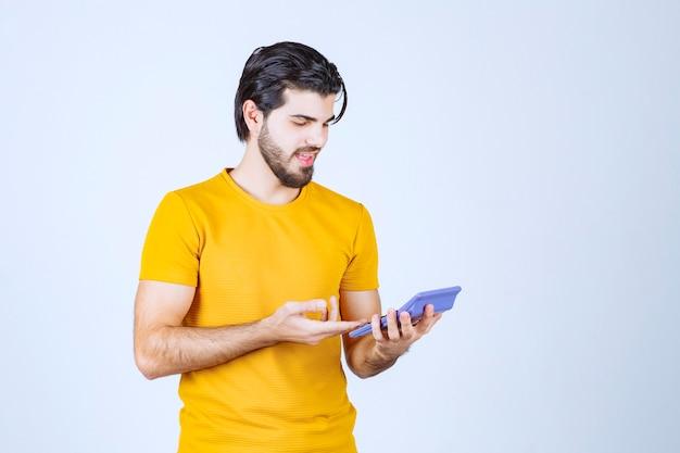 電卓で作業している男性は不満に見えます。