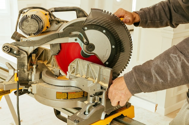 Man working with a circular saw cutting wooden board