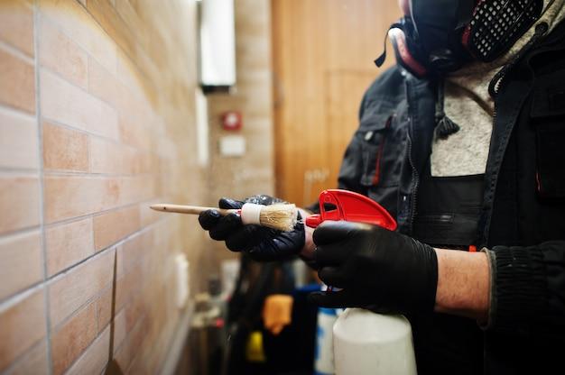 벽에 청소기 브러시를 사용하는 사람을 닫습니다.