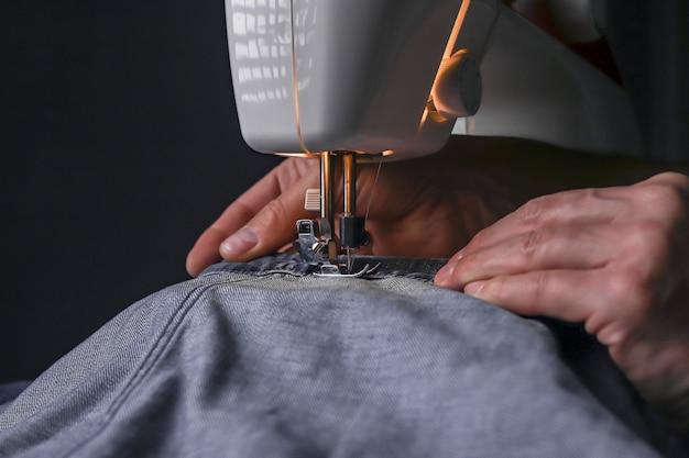 Человек, работающий с джинсовым материалом на швейной машине, крупным планом, дизайн одежды