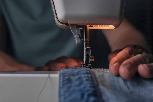 Человек, работающий с джинсовым материалом на швейной машине крупным планом модельер