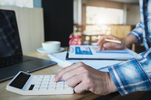 Человек работая с финансами высчитывает на калькуляторе и использует диаграмму данным по компьтер-книжки и документа компьютера в комнате офиса.