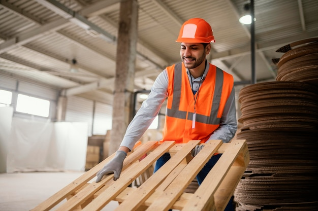 무거운 목재 재료로 작업하는 사람