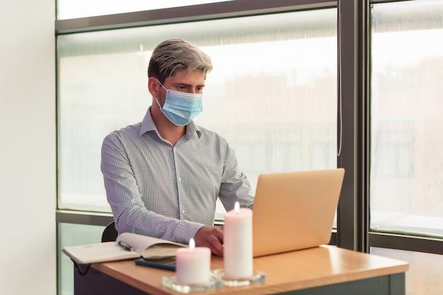 彼のオフィスで彼のラップトップで働いている男性は、covidウイルスのために衛生マスクを身に着けています。