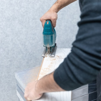 Man working with jigsaw on white wood laminate