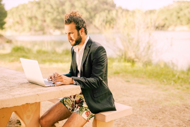 Man working with laptop against picturesque landscape