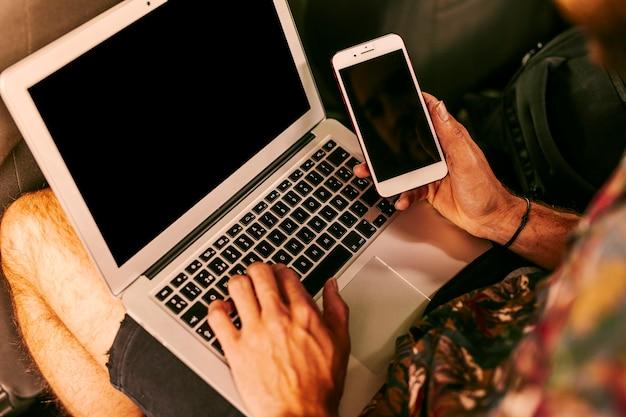 노트북 및 스마트 폰 사용하는 사람