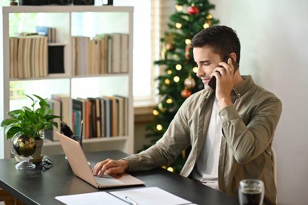 Человек, работающий с портативным компьютером и разговаривающий по мобильному телефону у себя дома.