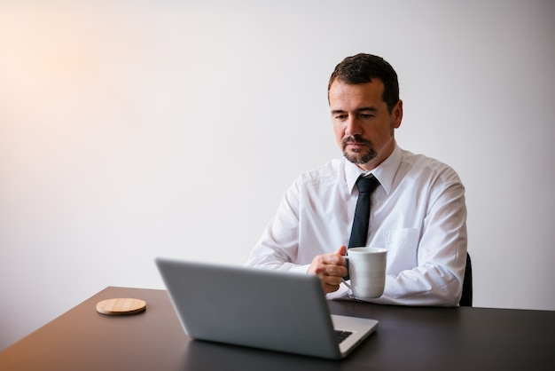 Man working with laptop at home, holding a cup of warm tea or coffee.