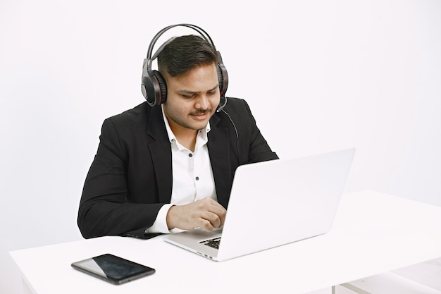 Man working with laptop. indian dispatch or hot line worker.