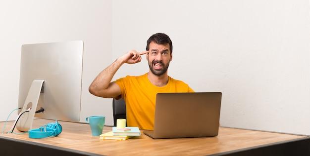Человек, работающий с laptot в офисе, делая жест безумия, положив палец на голову