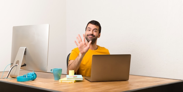Man working with laptot in a office counting five with fingers