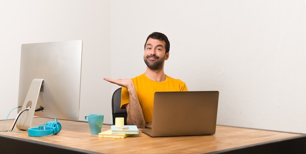 Man working with laptot in a office holding copyspace imaginary on the palm to insert an ad