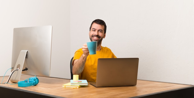 Man working with laptot in a office holding a cup of coffee