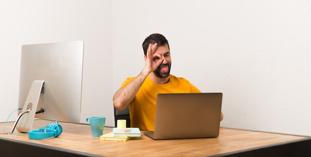 Man working with laptot in a office makes funny and crazy face emotion