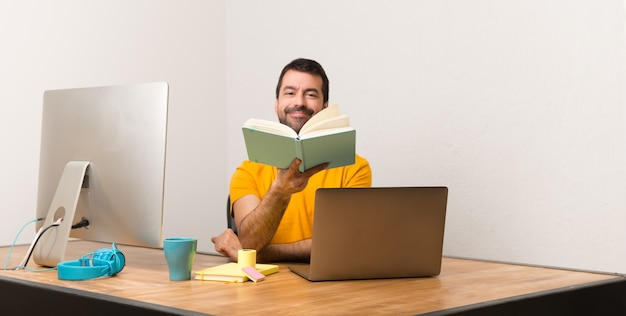 Man working with laptot in a office reading a book