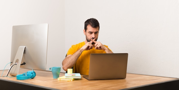 Man working with laptot in a office showing a sign of silence gesture