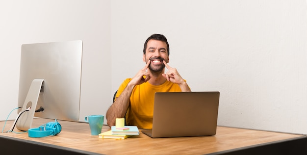 Man working with laptot in a office smiling with a happy and pleasant expression