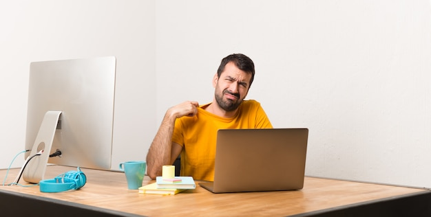 Man working with laptot in a office with tired and sick expression